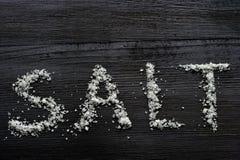 Grani di sale su una tavola di legno Fotografia Stock Libera da Diritti