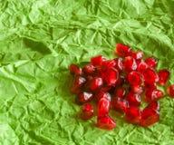 Grani maturi succosi rossi del melograno sul fondo del Libro Verde Fotografie Stock Libere da Diritti