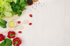 Granica świeże zieleni zielenie, czerwona papryka, czereśniowy pomidor, pieprz, olej i naczynia na miękkim białym drewnianym tle, Obraz Stock