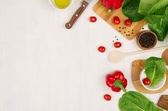 Granica świeże zieleni zielenie, czerwona papryka, czereśniowy pomidor, pieprz, olej i naczynia na miękkim białym drewnianym tle, Zdjęcie Royalty Free