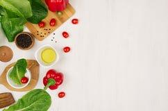 Granica świeże zieleni zielenie, czerwona papryka, czereśniowy pomidor, pieprz, olej i naczynia na miękkim białym drewnianym tle, Zdjęcia Stock