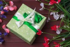 Granica kwiaty z Macierzystym ` s dnia prezenta pudełkiem i etykietką przeciw nieociosanemu drewnianemu tłu Obrazy Stock