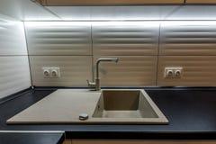Granietgootsteen en watertapkraan in nieuw modern keukenbinnenland Stock Afbeelding