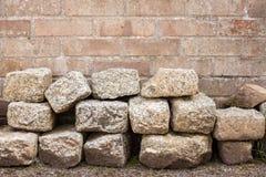 Granit-Blöcke angehäuft vor Backsteinmauer Stockfotografie