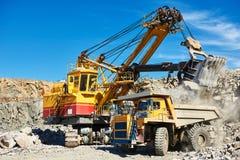 Granit ou minerai de chargement d'excavatrice dans le camion à benne basculante à ciel ouvert photos libres de droits