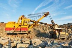 Granit ou minerai de chargement d'excavatrice dans le camion à benne basculante à ciel ouvert Photo libre de droits