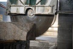 Granit som bearbetar i tillverkning Bitande granittjock skiva med en cirkelsåg Bruk av vatten för att kyla Industriellt såga av royaltyfria bilder