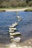 Granit som kliver stenar, korsar en flod Arkivfoto