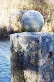 Granitboll på en sockel som täckas med frost royaltyfri foto