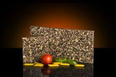 Granitcountertopen för två kök tar prov anseende på den glansiga svarta tabellen med matgarnering Kökcountertopbegrepp Royaltyfri Bild