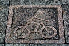 Granitcykeltecknet går på vägen Arkivbild
