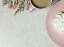 The granite background with cup of coffee, marshmallow on the the plate and flowers stock photography