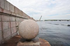 Granite ball on the waterfront of the river Neva and the open fo. Undry bridge in St. Petersburg, Russia Royalty Free Stock Images