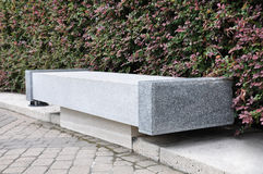 Granite Bench. A single empty granite bench sitting against a line of green and pink bushes Royalty Free Stock Images