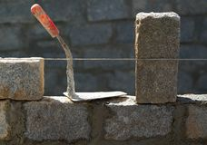 Granite blocks wall construction with mortar. Granite blocks wall construction with cement mortar and trowel tool stock photography