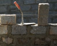 Granite blocks wall construction with mortar. Granite blocks wall construction with cement mortar and trowel tool royalty free stock photos