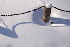 Granite bollard with metal chain in snow Royalty Free Stock Photography