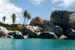 Granite boudlers and palm trees line turquoise waters Royalty Free Stock Photos