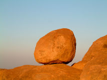 Granite boulder on blue sky. Huge granite boulder perched on rocks against blue sky Royalty Free Stock Images
