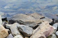 Granite Boulders Along The Lake Shoreline. A pile of granite rock boulders along a fresh water lake shoreline Royalty Free Stock Photography