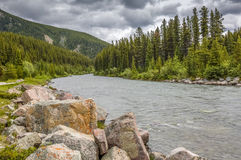 Granite Boulders Lining a Mountain River - Alberta, Canada. Granite boulders line the Athabasca River as it flows through the Rocky Mountains in Jasper National Stock Photo