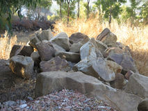 Granite boulders in sun dried field Royalty Free Stock Images