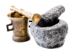 Granite and brass mortar with pestles on a white Stock Images