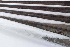 Granite brown stairs under the white snow.  Stock Image