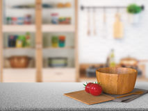 Granite counter top with tomato and wooden bowl Royalty Free Stock Photo