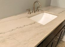 Granite countertop with white sink and chrome faucet on dark wood cabinets, tile floor inside bathroom stock images