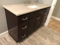 Granite countertop with white sink and chrome faucet on dark wood cabinets, tile floor inside bathroom stock photography