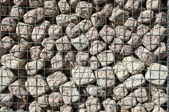 Granite cubes made of natural stone with a metal grid Stock Photos