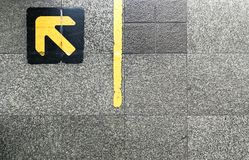 Granite floor with yellow arrow on top of black pad at queuing l. Ine in BTS skytrain station Royalty Free Stock Photography
