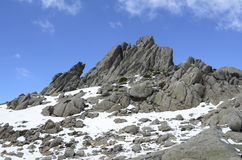 Granite formation over the summit and hillside covered with snow Stock Images