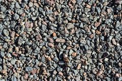 Granite gravel. Brown and gray crushed rocks for construction on the ground. Gravel macadam road texture or background. Royalty Free Stock Photos