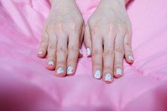 Granite Gray Nail. Close Up Nails Polish with Colourful Bead on Pink Blanket Background Royalty Free Stock Image