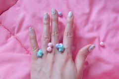 Granite Gray Nail. Close Up Nails Polish with Colourful Bead on Pink Blanket Background Royalty Free Stock Photo