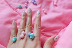 Granite Gray Nail. Close Up Nails Polish with Colourful Bead on Pink Blanket Background Royalty Free Stock Photos