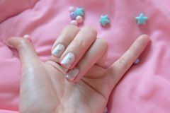 Granite Gray Nail. Close Up Nails Polish with Colourful Bead on Pink Blanket Background Stock Image