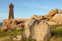 Granite lighthouse and rocks Stock Images
