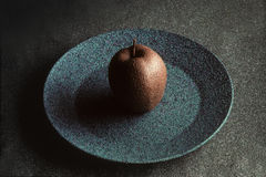 Granite-like sculpture of apple on a plate Stock Photos