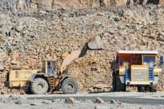 Granite mining. Wheel loader loading ore into dump truck at opencast. Granite mining. Heavy wheel loader excavator loading granite rock or iron ore into the huge royalty free stock image