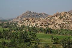 Granite mountain and rice paddy in Hampi Stock Photography