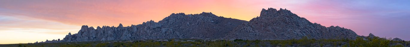 Granite Mountain Sunset Panorama. Sunset (facing westward) behind the Granite Mountains of the Mojave Desert National Preserve in California.  High-res stitched Stock Image