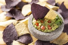 Granite Mulcajete filled with fresh guacamole surrounded by blue and yellow tortilla chips royalty free stock image