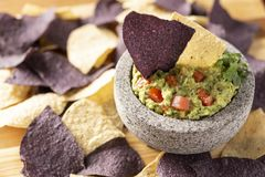 Granite Mulcajete filled with fresh guacamole surrounded by blue and yellow tortilla chips stock photo