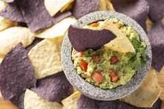 Granite Mulcajete filled with fresh guacamole surrounded by blue and yellow tortilla chips royalty free stock photos
