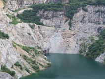 Granite open pit mining with blue green pond Stock Photography