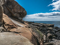 Granite Overhang and Distant Solitary Hiker, Schoodic Point Stock Images