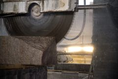 Granite processing in manufacturing. Cutting granite slab with a circular saw. Use of water for cooling. Industrial sawing of. Granite processing in stock photos